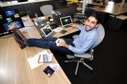 """The NQ Mobile offices at Travis Walk are pretty stereotypical of a new-age tech company: open desks, communal eating and meeting spaces, whiteboards, flat screen TVs and a pool table. That, combined with a heavy travel schedule, means Co-CEO Omar Khan doesn't have a permanent set up at his desk. We found most the items, like currency from a trip to Macau, in a backpack he """"borrowed"""" from his 10-year-old son."""