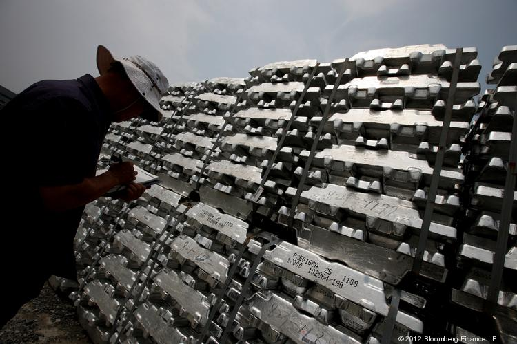 A worker inspects aluminum ingots stacked outside a warehouse.