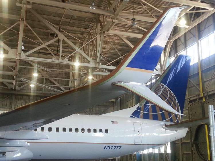 """These scimitar winglets, made by Aviation Partners Boeing, are an addition to existing blended winglets and feature the extended """"scimitar"""" tip. This is a photo of winglets on a plane inside a hangar at Moses Lake."""