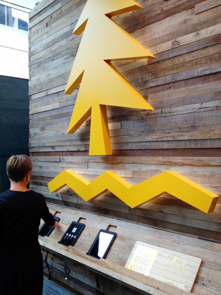 Umpqua Bank spokeswoman Eve Callahan looks over the iPad wall at the flagship branch opening Aug. 26 in San Francisco's financial district.