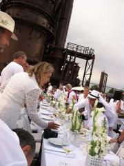 The crowd of Diner en Blanc diners hauled 400 yards down into Gas Works Park and set up at the prearranged place, which was only known shortly before the event. The set up was rapid, with each small group bringing its own tables, white linens and white chairs.