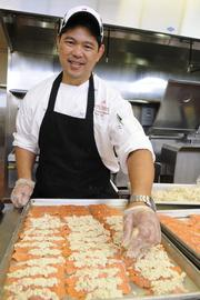 Nelson Kawai-Yamagata, sous chef at the Pomaikai Ballroom at Dole Cannery in Honolulu, prepares a pan of crab-crusted salmon.