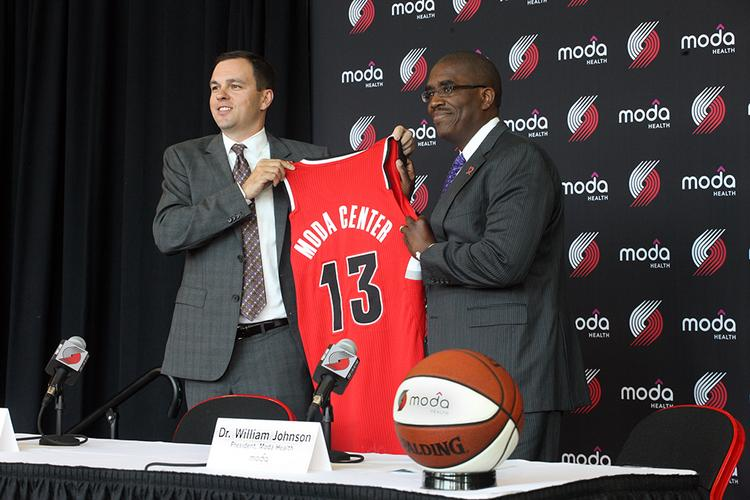 Moda Health President William Johnson and Portland Trail Blazers President Chris McGowan display a Blazers' jersey at a press conference announcing that Moda has acquired naming rights for the Rose Garden.