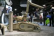 An iRobot Corp. 710 Warrior lifts a weight while on display.