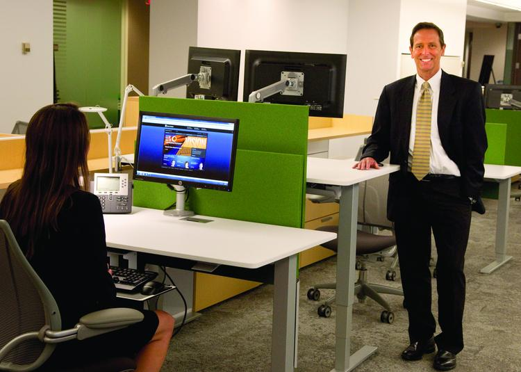 Banc Winsor, State Street Corp.'s director of realty services, stands in a cubicle area that features ergonomic seating with adjustable desks allowing employees to work seated or standing.