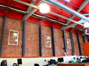 BlackArrow's 10,000 square-foot office with vaulted ceilings includes items —like the vintage white windows hanging here — that are borrowed from neighboring businesses owned by the same landlord.