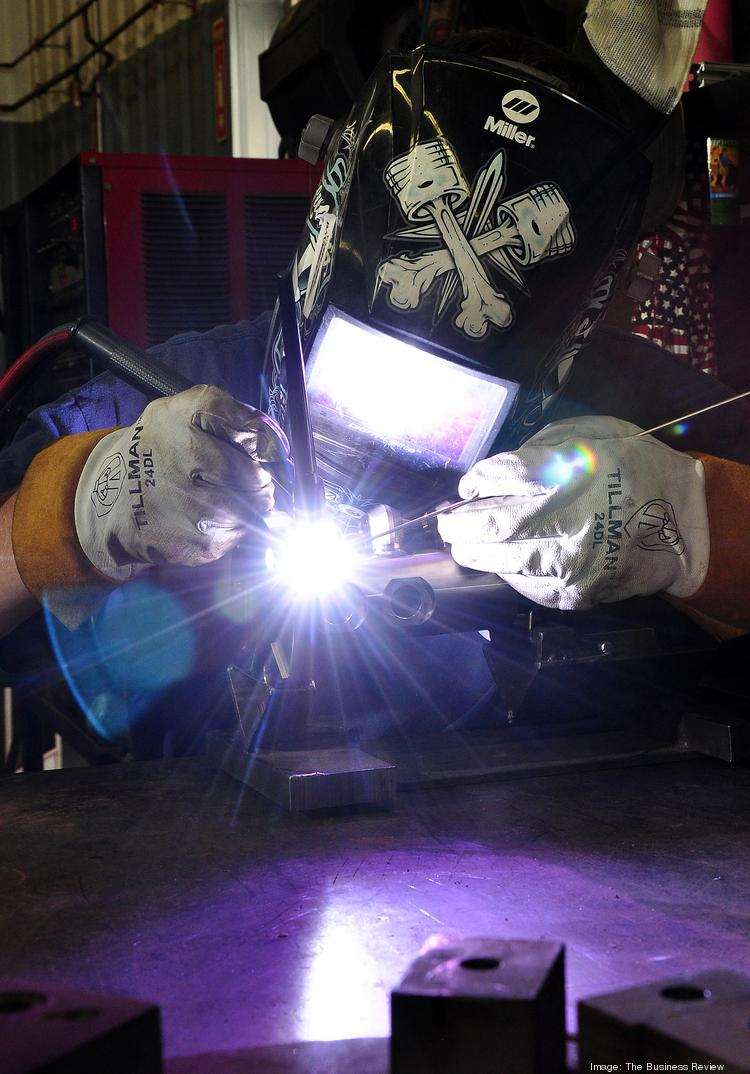 Andy Daubert welds at Ushers Machine & Tool Co. Inc., in Round Lake. He is one of 80 employees at the shop, which continues to hire as it wins more business from General Electric Co.