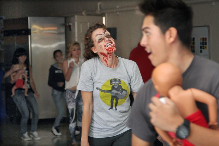 From left, teacher Hope Kitts, as a zombie, chases freshman Richard Marquez, age 14, holding a baby doll, during an emergency preparedness exercise at Health Leadership HS. The exercise showed how viruses can spread fast.