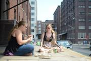 Web designers Chelsey Kosmatka (left) and Tonya Peck have lunch along N. Seventh Avenue outside Ackmann and Dickenson, a web design firm where they work.