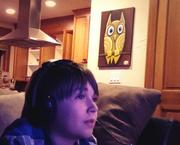 Reader Emily Papel's son plays video games while a Henry owl looks on.