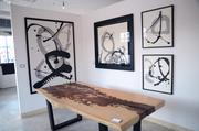 A suar wood table by Doro Designs complement framed ink pieces by Shan Hu Hou in one corner of Jai Gallery.