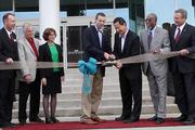 University of Cincinnati President Santa Ono is joined by university officials to cut the ribbon to open to new dormitory.