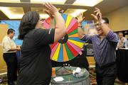 From left, Mary Bartley of Hawaiian Telcom, gives Ky Vuong of Hawaii News Now a high 10 after a spin and win at the Pacific Business News Small Business Growth Expo.