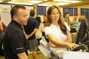 From left, Eddie Yates of Hawaiian Telcom assists Deanne August with services at the Pacific Business News Small Business Growth Expo at the Hawaii Convention Center.