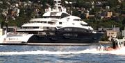 A U.S. Coast Guard inflatable boat speeds by the super yacht Serene before she docks in Seattle.