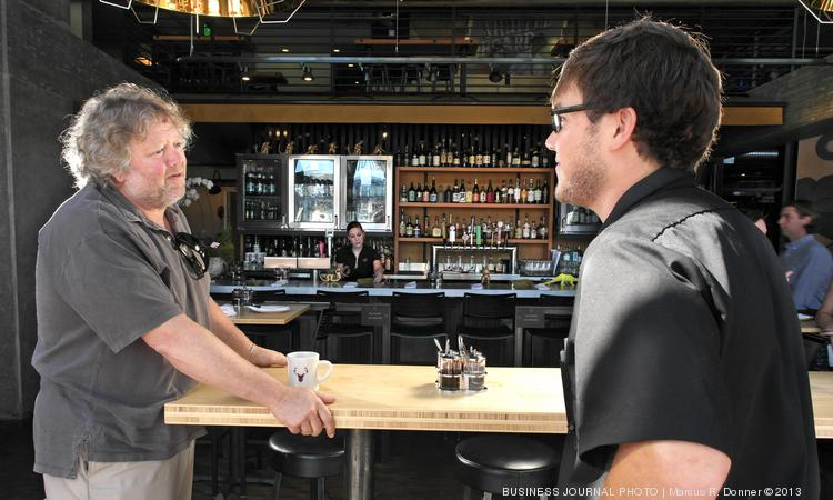 "Restaurateur Tom Douglas, left, reviews the year-old Seattle sick leave law with Cal Cruickshank, a server at Douglas' Tanakasan restaurant. Douglas considers the law ""an intrusion"" but said it has cost him only about one-third as much as projected for the 650 eligible employees in his company. In part, he says, that's because servers often switch shifts when they're ill rather than taking paid time off. That's what Cruickshank does; he has worked at Tom Douglas' Restaurants for a year — and not used any of his paid sick days."