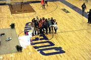 The womens' basketball team poses for an impromptu photo in the new gymnasium.