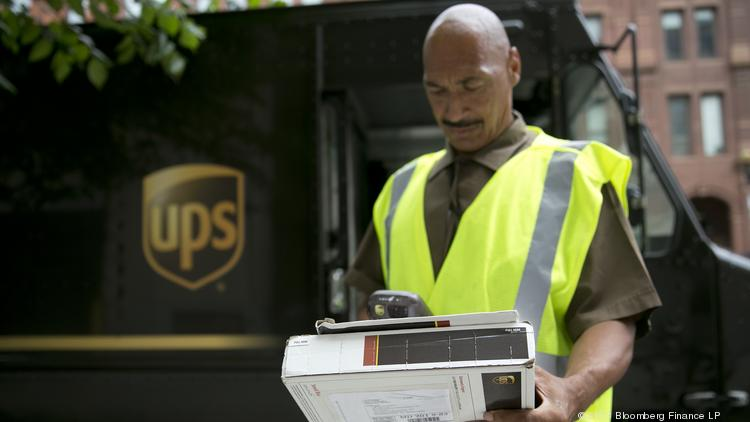 United Parcel Service Inc. employee Eric Brooks scans a package while making a delivery in Washington, D.C., U.S., on Monday, July 22, 2013.