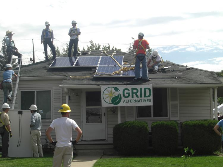 Volunteers with the nonprofit Grid Alternatives, which installs solar power systems on the roofs of low-income families, on a Denver project in August 2013.
