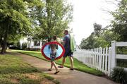 A father and son walk from the Community Center swimming pool to their home.