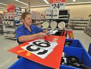 Joanne Kinner, zone manager, changes the numbers on a price sign at the store
