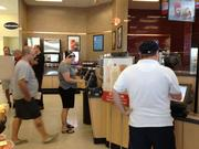 Customers line up at touch-screen kiosks to order breakfast at Wawa's deli on the east Orlando store's Aug. 22 opening day.