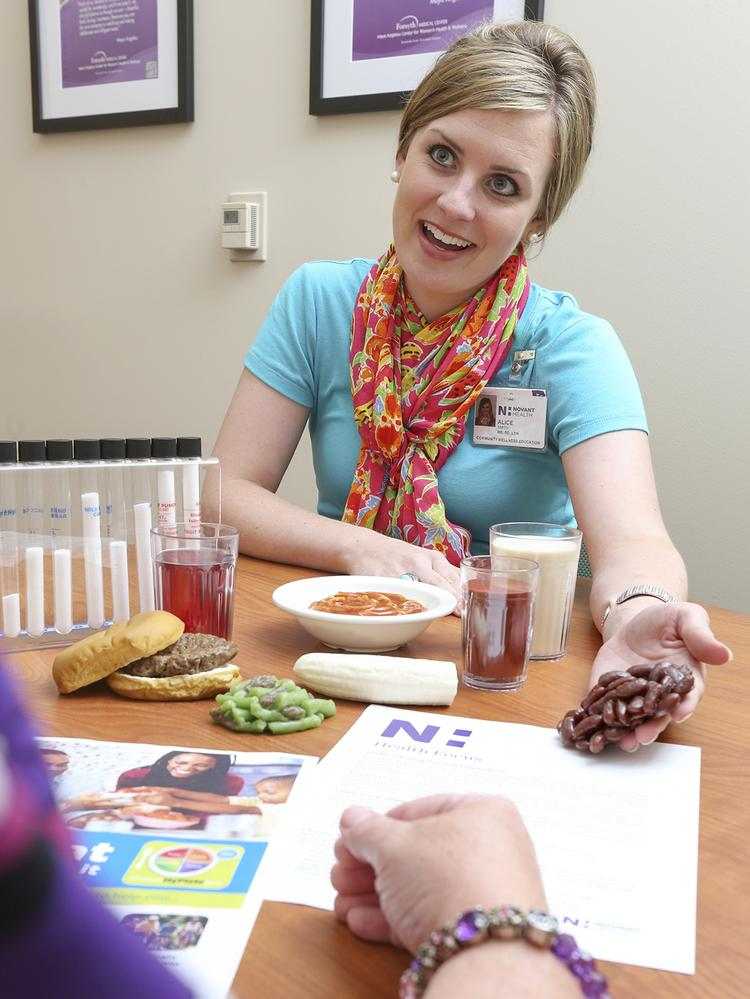 Alice Smith, Novant Health community wellness educator, consults a diabetes patient at the Maya Angelou Women's Health Center.