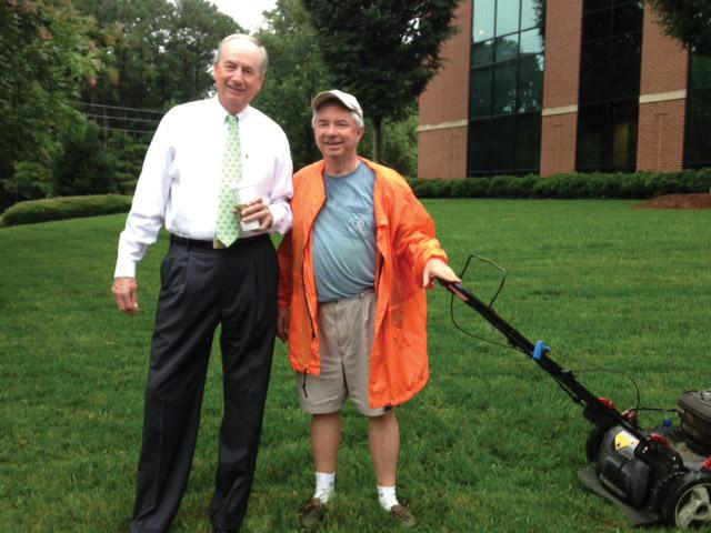 Bob Hatley, left, enjoyed watching Thad Woodard, right, mow his bank's front lawn.