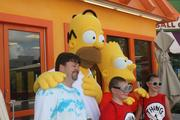 Homer and Bart Simpson pose with guests.