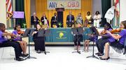 A group of student violinists from the Cathedral Arts Project play music at Central Riverside Elementary School on Thursday, Aug. 22, 2013.