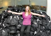 Sandra Lahti, assistant escrow officer at First American Title, displays a pile of backpacks full of school supplies the company will donate to kids in need.