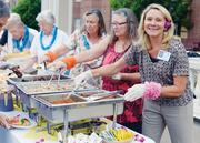 Susanne Nee, transitions nurse for Augustana Care, serves food during a Hawaiian-themed event put on for residents.