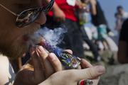 A man who says he is a medical marijuana patient takes a hit off his pipe at Hempfest at Myrtle Edwards Park and Centennial Park in Seattle on Aug. 18, 2013.