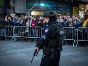 In New York City, police keep tabs on Times Square as Mayor Bill de Blasio and NYPD Commissioner William Bratton talk to reporters about increased security in the parts of the city following the Belgium terror attacks.