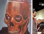 Orlando artist Plimio Marcos Pinto talks to visitors at his booth in Artist Alley.