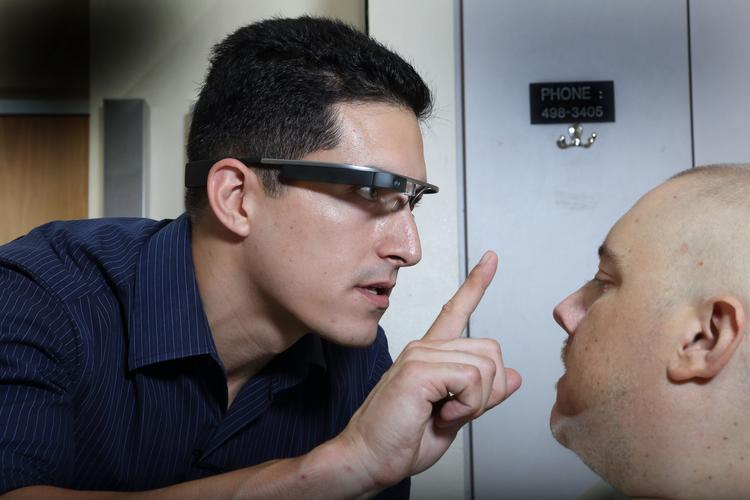 Stanford Hospital doctor Errol Ozdalga begins working with a patient and transmits the physical therapy session through Google Glass. The interaction is viewed by a classroom of medical students, who are taking notes on proper bedside manner.