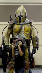 A Mandalorian warrior from the Star Wars Expanded Universe waits as his younger counterpart adjusts his headgear.