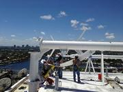 Workers install wind turbines at the top of Hilton Fort Lauderdale Beach Resort.