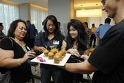 From left, Lucy Quisano of Queen's Medical Center, Susan Nillias of the Department of Health and Tami Hattori of B2C Hawaii try the bacon cheddar mini burgers at PBN's Pau Hana event at the Modern Honolulu in Waikiki.