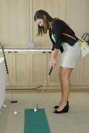 Paulina Sirgo of Staffing Solutions of Hawaii tries her hand at a golf putt at the PBN Pau Hana at the Modern Honolulu in Waikiki.