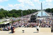 Al Sharpton speaks to a crowd on the mall with the Washington Monument in the background.