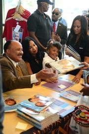 Martin King III gets help at his book signing from daughter Yolanda and his wife Andrea.