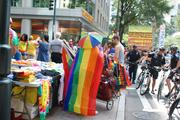 A rainbow-cloaked vendor sells shirts and other merchandise on the sidewalk as police offers keep an eye on protests taking place nearby.