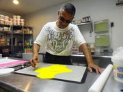 Rise Cupcakes employee Wilson Rodriguez working in the store's prep area