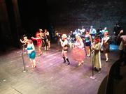 The New Century Follies burlesque group used smartphones as props in their opening dance number to help encourage the audience to use the interactive Center Screen app.