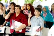 In front, from left, Rita Mora and Honz Truong take the oath of allegiance along with 19 others to become U.S. citizens at a naturalization ceremony Monday at the Refugee Women's Alliance in Seattle.  Secretary of the Interior Sally Jewell gave the keynote address.