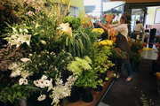 Sarah Blasi arranges flowers at the entrance to New Seasons Market on North Williams. The grocery is next to a hospital.