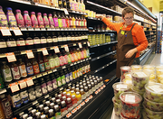 Audra Thiebout of New Seasons Market helps set up the company's newest store, which opened Wednesday on North Williams.