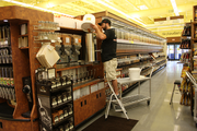 A worker tops off the honey dispenser in the bulk section of Portland's newest New Seasons Market. The store opened Wednesday on North Williams.