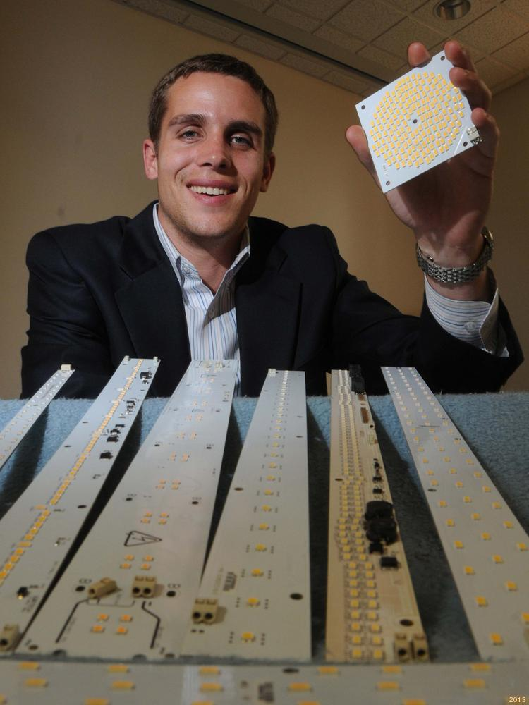 Sean Darras of Luxtech makes premium LED engines. He's holding a square array of LEDs, and the strips in front of him are also LEDs. They get fitted into light fixtures by his customers for a variety of designs. Photo / Curt Hudson